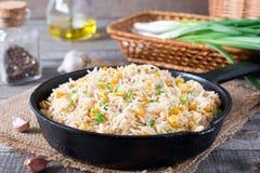 亚洲人炒饭用鸡蛋和玉米在一个煎锅在木背景 库存图片