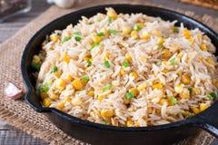 亚洲人炒饭用鸡蛋和玉米在一个煎锅在木背景 免版税图库摄影
