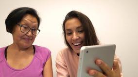 亚洲人退休了做与片剂小配件的母亲和年轻女儿滑稽的selfie照片 4K 股票视频