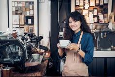亚洲人Barista供食了咖啡与微笑在咖啡馆藏品杯子用两有笑容的手在咖啡厅背景 库存图片