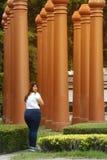 亚洲俏丽的兴高采烈的走面孔肥胖妇女的姿势和拿着一本小册子 免版税库存照片