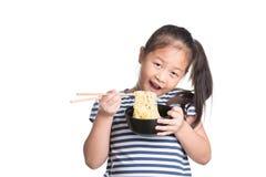 亚洲儿童女孩年龄7年,吃在白色b的方便面 免版税库存照片