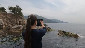 亚洲出现的女孩在一个多岩石的海滩站立在土耳其并且为美好的landsc照相 股票录像