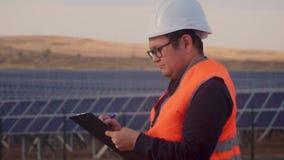 亚洲出现的工程师在一件白色盔甲和橙色背心的,在一个领域在企业中站立,审查和 影视素材