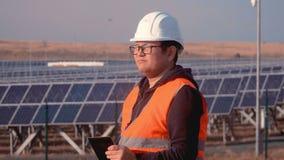 亚洲出现的工程师在橙色背心和安全帽身分的在与太阳电池板和工作的领域旁边 股票录像