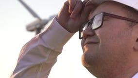 亚洲出现的工程师是在风车附近,并且看看在太阳发光的他的面孔的工作 股票视频