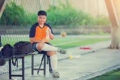 亚洲十几岁的男孩饮用水画象在足球场的在训练以后 图库摄影