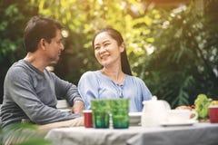 亚洲可爱的夫妇退休有幸福谈话在晚餐期间在后院 在退休以后的幸福家庭 库存图片