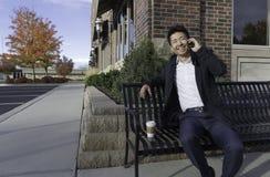 亚洲商人微笑和谈话在长凳的手机 库存照片