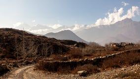 亚洲在路附近的山小村庄在更低的野马的秋天,尼泊尔,喜马拉雅山,安纳布尔纳峰保护地区 库存照片