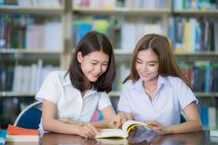 亚洲夫人学生研究,并且在图书馆里回家工作在Universi 库存照片
