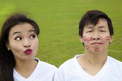 亚洲夫妇滑稽的亲吻 免版税库存图片