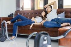 亚洲夫妇疲倦了对与vaccuum擦净剂的清洗的地板 库存图片