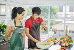 亚洲夫妇站立烹调在厨房里 拿着片剂的妇女微笑 人采摘在碗的菜准备沙拉fo 免版税图库摄影