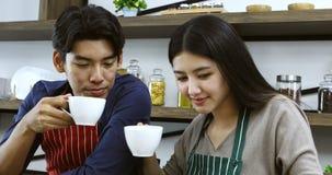 亚洲夫妇饮用的咖啡在厨房里一起 股票录像