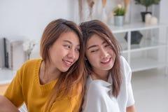 亚洲女同性恋的lgbt夫妇拥抱和坐床在白色windo附近 库存照片