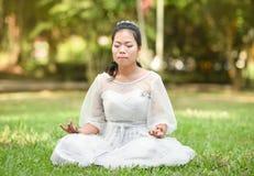 亚洲女子在绿草的瑜伽凝思 库存图片