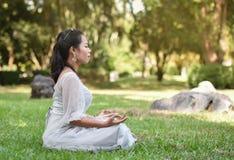 亚洲女子在绿草的瑜伽凝思 免版税库存图片