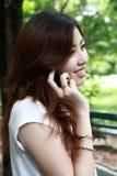 亚洲女孩电话俏丽联系 免版税库存照片