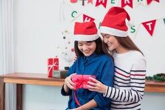 亚洲女朋友戴在圣诞快乐党的圣诞老人帽子和前 免版税图库摄影