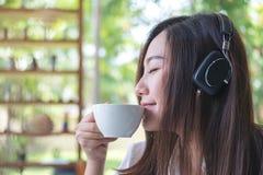 亚洲妇女关闭她的眼睛和听到与耳机的音乐,当喝与感到的咖啡愉快时和在与g的咖啡馆放松 库存照片