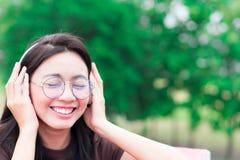 亚洲妇女听的音乐和微笑与耳机为放松 库存图片