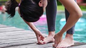 亚洲妇女实践瑜伽姿势常设手抓住脚趾关闭  免版税库存照片
