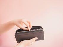 亚洲妇女手举行和插入物金钱在她的蓝色钱包有pi的 库存照片