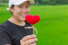 亚洲妇女手举行美丽的红色心脏甜点 免版税库存图片