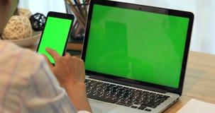 亚洲妇女手固定的单元电话 电话和膝上型计算机在书桌上有绿色屏幕的