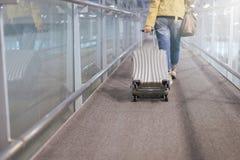 亚洲妇女旅客扯拽继续行李手提箱在走到登机口的机场走廊 免版税库存照片