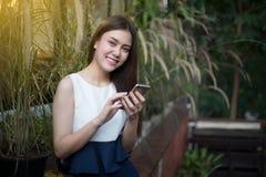 亚洲妇女是微笑和使用机动性并且接触巧妙的电话f 图库摄影