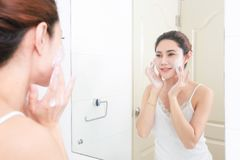 亚洲妇女清洁面孔皮肤开心与泡影cleansi 免版税库存图片