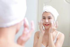 亚洲妇女清洁面孔皮肤开心与泡影cleansi 免版税库存照片