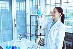 亚洲妇女科学家看看试管在她的手上有分析蓝色液体的蓝色手套的 免版税库存照片