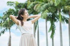 亚洲妇女立场在庭院里激动生气勃勃与蓝天和云彩的早晨 免版税库存图片