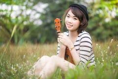 亚洲妇女纵向演奏尤克里里琴的在草甸 免版税库存照片