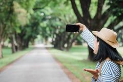 亚洲妇女背包旅客用途流动selfie,当旅行的a 图库摄影