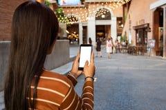 亚洲妇女藏品智能手机,当走在街道上时 免版税库存图片