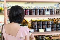 亚洲妇女购买巧克力在商店 库存图片