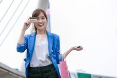 亚洲妇女购物微笑和藏品信用卡和购物 免版税库存图片