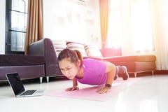 亚洲妇女锻炼做在家增加锻炼 免版税库存照片