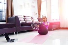 亚洲妇女锻炼做在家v上升吸收锻炼,与使用 图库摄影