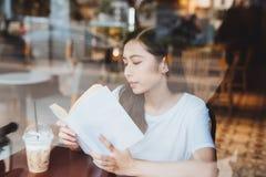 亚洲妇女阅读书葡萄酒颜色口气 观看通过风 库存图片