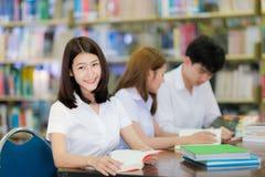 亚洲学生夫人微笑和读一本书在universit的图书馆里 免版税图库摄影