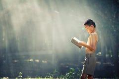 亚洲学生阅读书在泰国乡下,农村chil 免版税库存图片