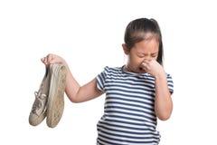 亚洲孩子女孩年龄7在白色背景的年举行腐败的鞋子 免版税库存照片