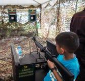 亚洲孩子射击模拟器机枪 免版税图库摄影