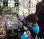 亚洲孩子射击模拟器机枪 免版税库存图片