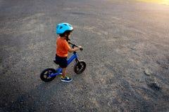 亚洲孩子第一辆天戏剧平衡自行车 免版税图库摄影